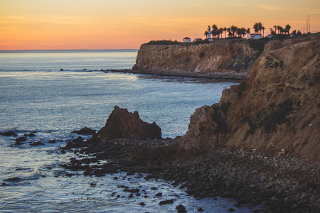 Scenic coastal view of Point Vicente Lighthouse atop the steep cliffs of Rancho Palos Verdes, California, with a colorful sky at sunset