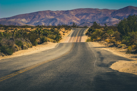 Wide open road in the middle of the desert of Joshua Tree National Park with view of San Bernardino Mountains, Riverside County, California
