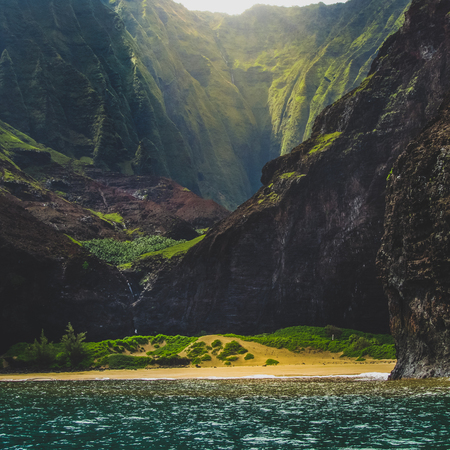 Stunning view of secluded Kalalau Beach and Kalalau Valley from a boat on a sunny day, Na Pali Coast, Kauai, Hawaii Archivio Fotografico