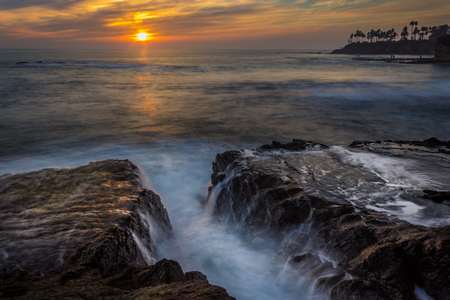 Beautiful coastal view of a colorful sky at sunset with stunning blue water, waves crashing into rock formations, and water from tide pools reflecting the sky, Diver's Cove, Laguna Beach, California Stock Photo