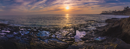 Beautiful coastal panorama of a colorful sky at sunset with stunning blue water, waves crashing into rock formations, and water from tide pools reflecting the sky, Diver's Cove, Laguna Beach, California