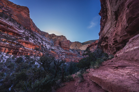 Low-angle view of colorful Fay Canyon with patches of snow covering the rock walls and shadows cast throughout the canyon as the sun sets, Coconino National Forest, Arizona Stock Photo