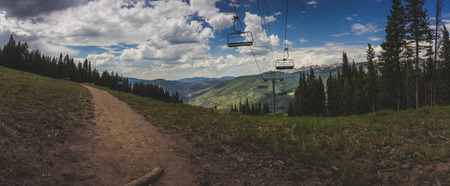 Breathtaking view of a hiking trail, coniferous trees, an idle ski lift in summer atop Vail Mountain, with a panorama of the Rocky Mountains in the backdrop, Vail, Colorado