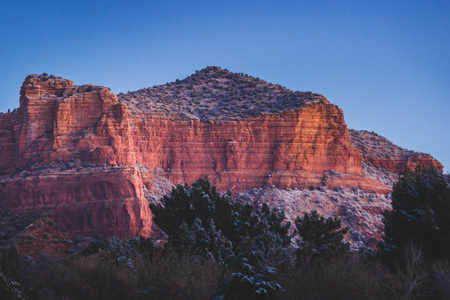 Red rock formations covered with patches of snow at sunrise with clear sky, Coconino National Forest, Arizona