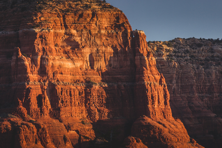 Majestic red rock formations with dramatic shadows at sunrise with clear sky, Coconino National Forest, Arizona