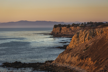Colorful coastal view of tall cliffs and ocean at sunset with layers of mountains in the background, Golden Cove, Rancho Palos Verdes, California