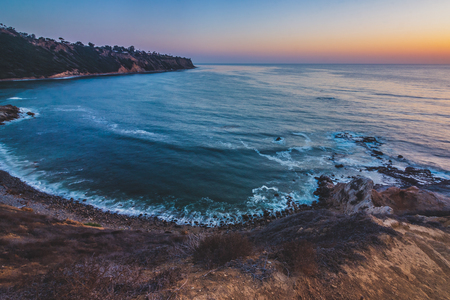 Colorful, long-exposure, elevated view of Bluff Clove with waves crashing onto the shore after sunset, Palos Verdes Estates, California