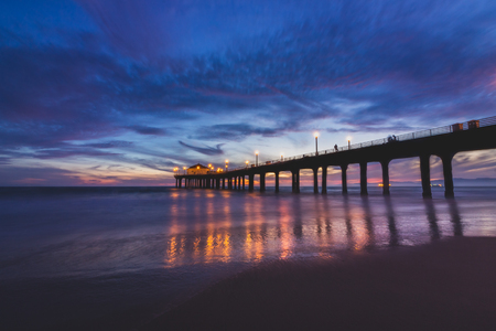 Long-exposure shot of colorful sky and clouds over Manhattan Beach Pier after sunset with smooth waves washing onto the beach, Manhattan Beach, California Stock fotó