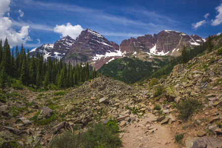 Majestic Maroon Bells peaks seen from the rugged Crater Lake Trail on a sunny day with blue sky in summer near Aspen, Colorado Stock Photo