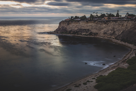 Long-exposure coastal view of tall cliffs of Lunada Bay with waves crashing onto the shore after sunset, Palos Verdes Estates, California