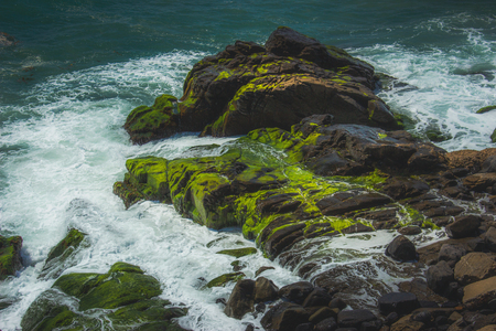 Waves crashing into rock formations covered with green algae, Point Mugu, California