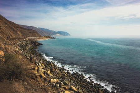 Iconic View of Pacific Coast Highway winding along the Southern California coast with the Santa Monica Mountains on one side of the road and Pacific Ocean on the other