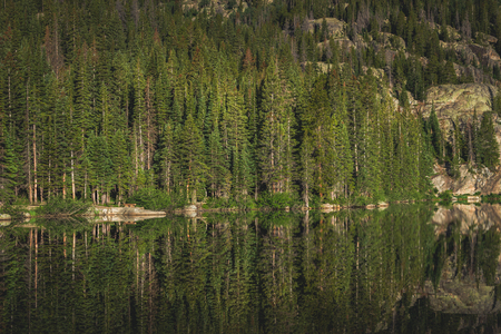 Perfectly calm water on Bear Lake with reflections of mountain and trees, Rocky Mountain National Park, Colorado