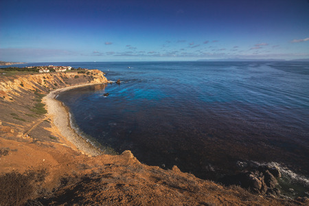 Elevated coastal view of Pelican Cove looking down at the rocky shoreline on a sunny day with Santa Catalina Island in the distance, Rancho Palos Verdes, California Imagens