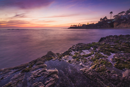 Beautiful coastal view of a colorful sky at sunset with stunning blue water, waves crashing into rock formations, and water from tide pools reflecting the sky, Divers Cove, Laguna Beach, California