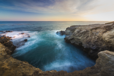 Stunning long-exposure view of smooth waves crashing into rock formations at sunset, Sequit Point, Leo Carrillo State Beach, Malibu, California Stock Photo