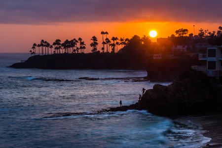 Beautiful coastal view of a colorful sky at sunset with waves crashing into rock formations and silhouette of palm trees, Divers Cove, Laguna Beach, California Stock Photo