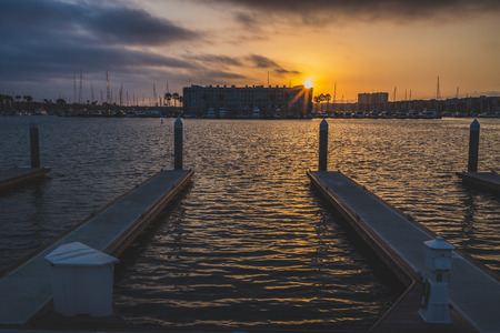 Dramatic clouds and colorful sky at sunset with calm water surrounding rows of piers, Burton Chace Park, Marina del Rey, California