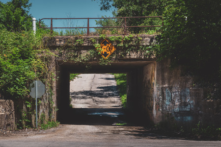 Old and narrow railroad underpass covered with graffiti and ivy leaves, LaPorte, Indiana