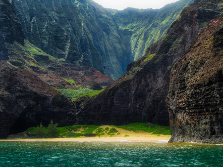 Stunning view of secluded Kalalau Beach and Kalalau Valley from a boat on a sunny day, Na Pali Coast, Kauai, Hawaii 免版税图像