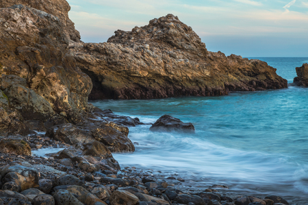 Long exposure of smooth waves crashing onto rock formations on Terranea Beach at sunset, Rancho Palos Verdes, California Imagens