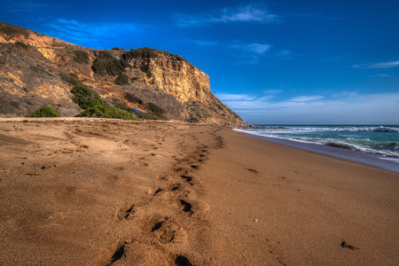 Tall cliffs surrounding Rancho Palos Verdes Beach with a trail of footsteps in the sand, Rancho Palos Verdes, California Stok Fotoğraf