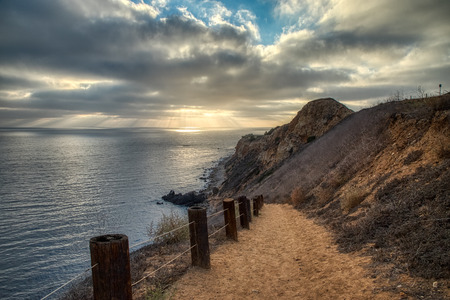 Dramatic view looking down the steep Tovemore Trail from the top of the rugged cliffs of Pelican Cove with beams of sunlight shining through the clouds, Rancho Palos Verdes, California