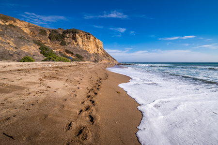 Tall cliffs surrounding Rancho Palos Verdes Beach with a trail of footsteps in the sand, Rancho Palos Verdes, California Imagens