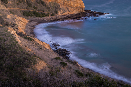 Long exposure photo of Inspiration Point cliff at sunset with waves crashing onto the rocks below Abalone Cove Shoreline Park, Rancho Palos Verdes, California Imagens