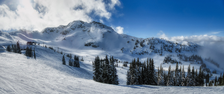 Stunning view of Whistler Mountain peak on a sunny day with clouds rolling through the mountaintop, Whistler Blackcomb Ski Resort, Whistler, British Columbia, Canada Stock Photo