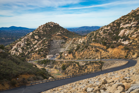 Stunning elevated view from Green Valley Truck Trail of a boulder-covered dam with mountains in the distance, Blue Sky Ecological Reserve, Poway, California