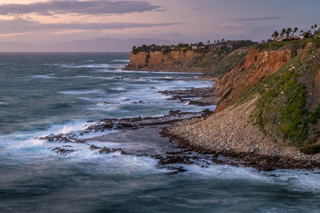 Long exposure shot of waves crashing into the tall cliffs along the Southern California coast at sunset on a windy day, Golden Cove, Rancho Palos Verdes, California