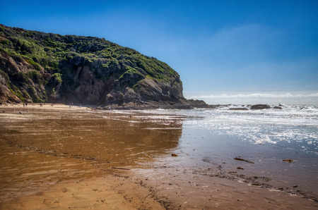 Picturesque coastal view of giant cliffs at Stands Beach on a sunny day with reflections in the water, Dana Point, California