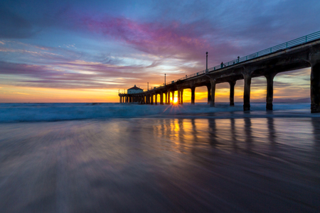Long-exposure shot of colorful sky and clouds over Manhattan Beach Pier at sunset with smooth waves washing onto the beach, Manhattan Beach, California
