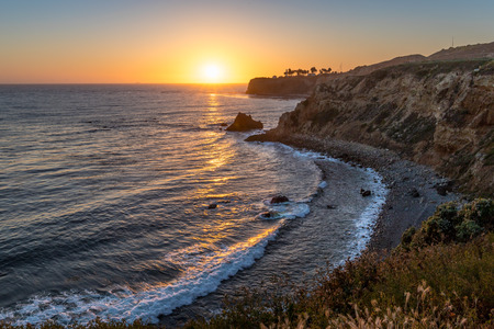 Long-exposure coastal view of Pelican Cove and Point Vicente Lighthouse with dramatic sky at sunset from Terranea Trail, Rancho Palos Verdes, California
