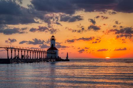 Oszałamiający zachód słońca z dramatycznymi chmurami nad Michigan City East Pierhead Lighthouse, Washington Park Beach, Michigan City, Indiana Zdjęcie Seryjne