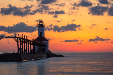Long exposure shot of Michigan City East Pierhead Lighthouse after sunset with colorful sky and dramatic clouds, Washington Park Beach, Michigan City, Indiana