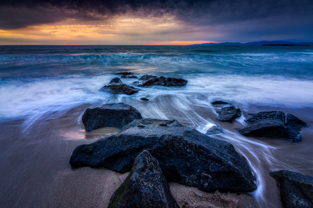 Long-exposure photograph of silky smooth water flowing around rock formations at sunset with dramatic clouds in the sky, Redondo Beach, California Stock Photo