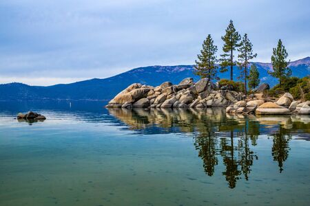 Tall trees atop beautiful boulders and crystal clear water at Sand Harbor with stunning mountains in the background, Lake Tahoe, Carson City, Nevada
