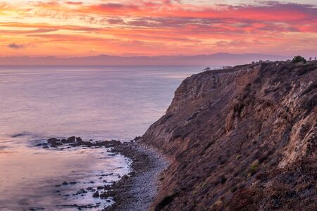 Colorful coastal view of rugged cliffs of Vicente Bluffs Reserve after sunset with pink and purple sky and Santa Monica Mountains in the distance, Rancho Palos Verdes, California Imagens