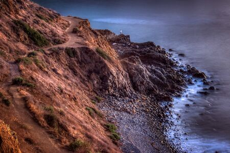 Long-exposure shot of smooth waves crashing into Flat Rock Point rock formations and Bluff Cove Trail after sunset, Palos Verdes Estates, California