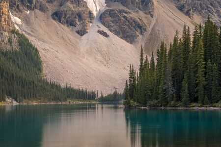 Stunning view of tall trees and mountain with reflections in the turquoise-blue water of Moraine Lake, Banff National Park, Alberta, Canada Reklamní fotografie