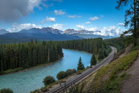 Beautiful view overlooking Bow Valley with railroad tracks running alongside the turquoise-colored Bow River, Banff National Park, Alberta, Canada