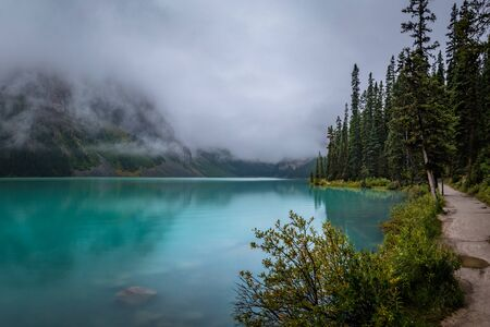 Scenic view of Lake Louise and Fairview Mountain with trees surrounding the lakeshore on a foggy day, Banff National Park, Alberta, Canada