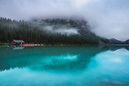 Scenic view of a cabin on the turquoise-colored Lake Louise with reflections of the surrounding mountains on a foggy day, Banff National Park, Alberta, Canada