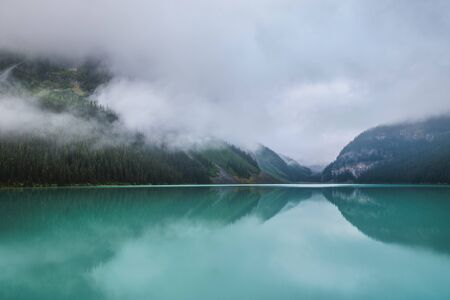 Turquoise-colored Lake Louise with reflections of the surrounding mountains on a foggy day, Banff National Park, Alberta, Canada