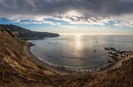 Beautiful coastal seascape of rugged Bluff Cove with dramatic clouds in the sky and waves washing onto the rocky shoreline, Bluff Cove Trail, Palos Verdes Estates, California