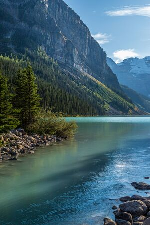 Majestic turquoise colored Lake Louise surrounded by towering mountains and glaciers in the distance, Banff National Park, Alberta, Canada Stockfoto - 136756714