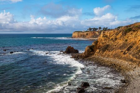 Coastal view of Pelican Cove with waves crashing onto the rocky shoreline and beautiful blue sky, Terranea Trail, Rancho Palos Verdes, California Imagens