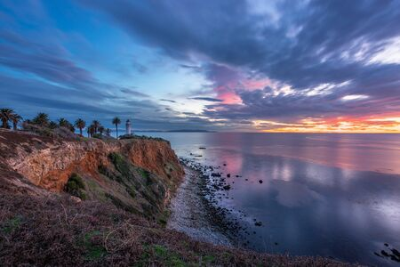 Gorgeous long exposure clifftop view of Point Vicente Lighthouse after sunset with colorful clouds in the sky and calm waves washing onto the rocky shoreline, Rancho Palos Verdes, California Imagens